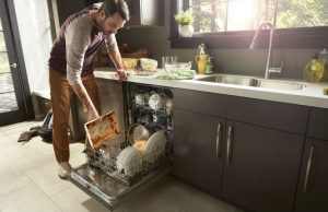 Image of a person placing dirty dishes in a dishwasher