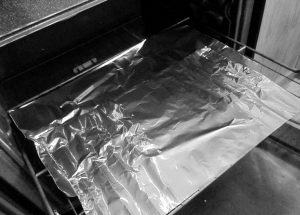 Image of an open oven with aluminum foil on the grill