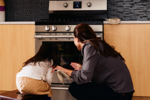 Image of two people in front of an oven