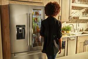 Image of a woman standing next to a refrigerator