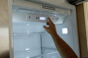 Image of a hand pressing a button inside a refrigerator.